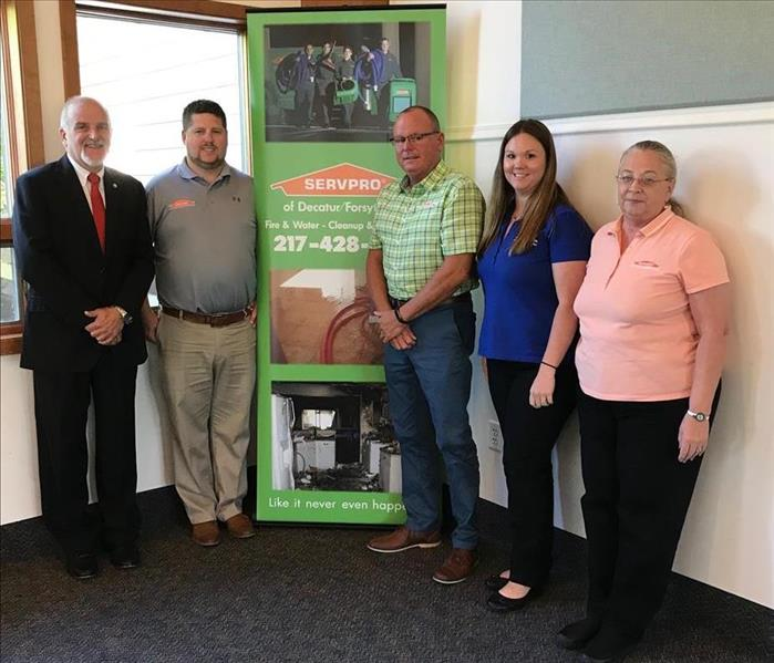 SERVPRO of Decatur/Forsyth employees standing by the SERVPRO floor banner.
