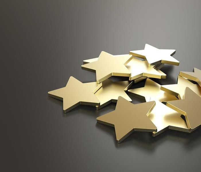 gold stars in a pile with a gray background.