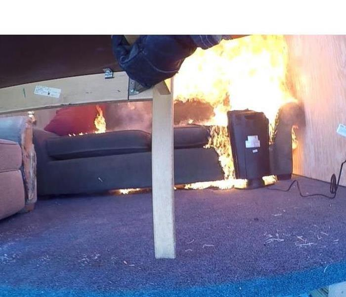 Space heater on fire in a living room next to a couch.