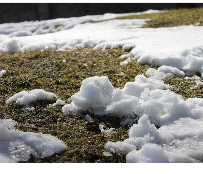 Snow melting on grass.