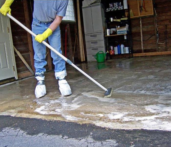 A person cleaning grease off a garage floor with soap and a scrub brush.