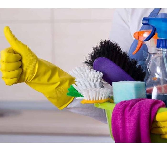 A person carrying cleaning supplies. The person is wearing yellow gloves.