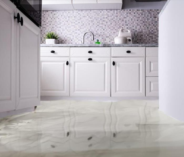 white kitchen cabinets with sanding water on the floor.