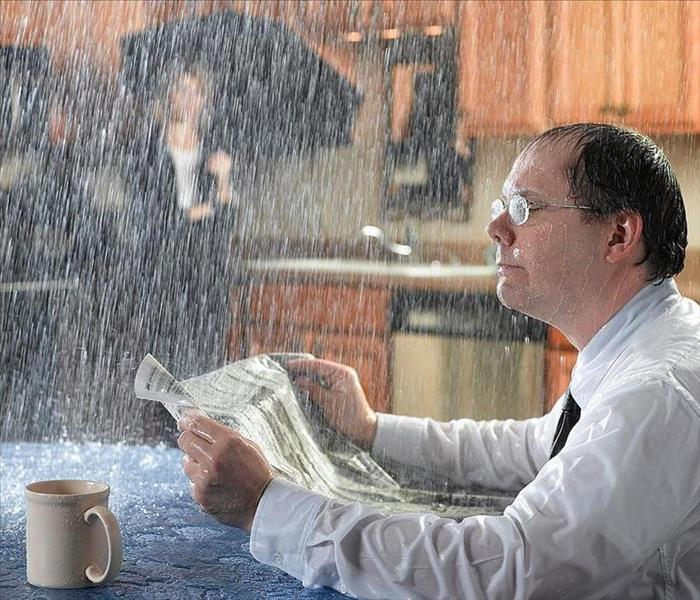 A man sitting in the kitchen at the table reading a paper with water pouring down on him.