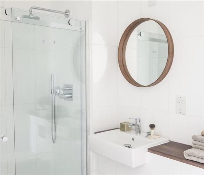 White bathroom with glass shower doors.